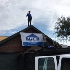 a roof leak repair specialist is on top a roof