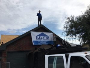 a roof leak repair specialist is on top a residential roof